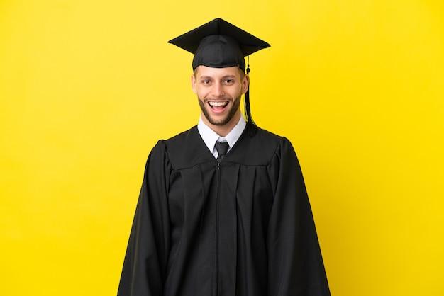 Giovane uomo caucasico laureato isolato su sfondo giallo con espressione facciale a sorpresa