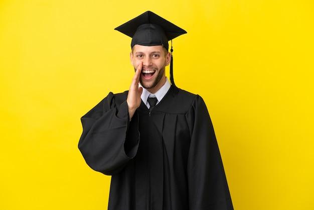 Giovane uomo caucasico laureato isolato su sfondo giallo con espressione facciale sorpresa e scioccata