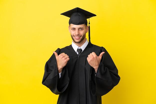 Giovane uomo caucasico laureato isolato su sfondo giallo con il pollice in alto gesto e sorridente