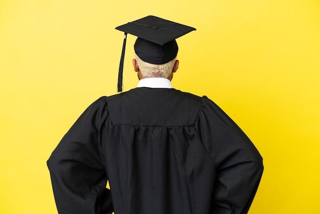 Giovane laureato uomo colombiano isolato su sfondo giallo in posizione posteriore