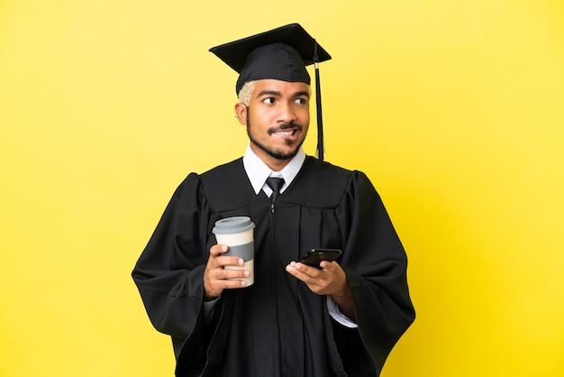 Giovane laureato colombiano isolato su sfondo giallo che tiene il caffè da portare via e un cellulare mentre pensa a qualcosa