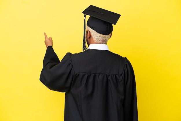 Giovane laureato uomo colombiano isolato su sfondo giallo che punta indietro con il dito indice