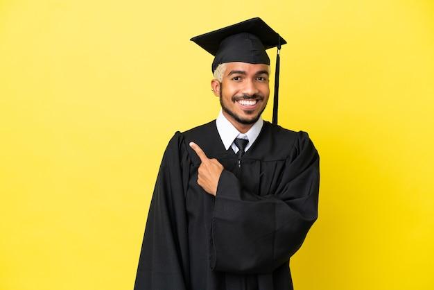 Giovane laureato colombiano isolato su sfondo giallo che punta al lato per presentare un prodotto