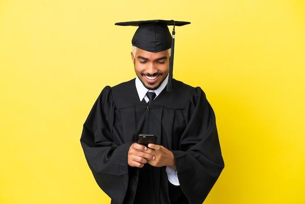 Giovane laureato colombiano isolato su sfondo giallo che invia un messaggio con il cellulare