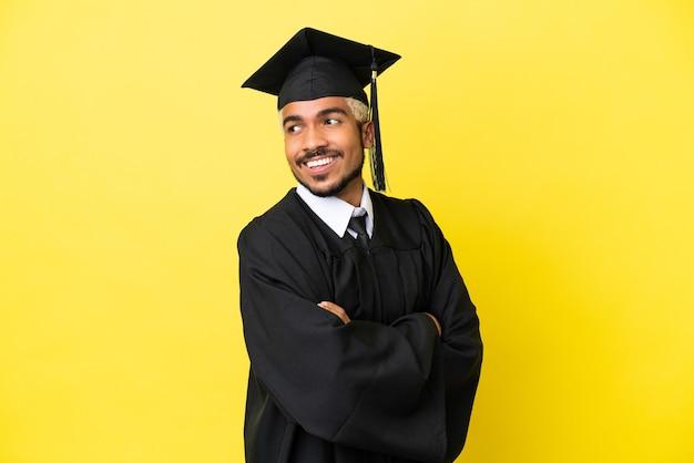 Giovane laureato colombiano uomo isolato su sfondo giallo con le braccia incrociate e felice