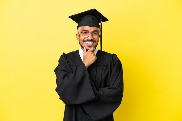 Giovane laureato uomo colombiano isolato su sfondo giallo con gli occhiali e sorridente