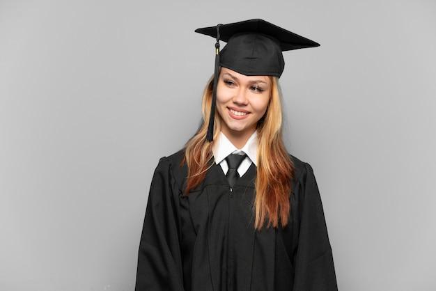 La giovane ragazza laureata ha isolato il fondo che guarda al lato e che sorride