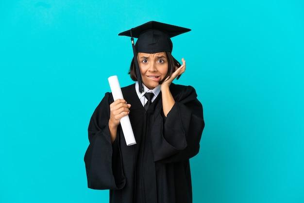 Giovane ragazza laureata su sfondo blu isolato frustrata e che copre le orecchie