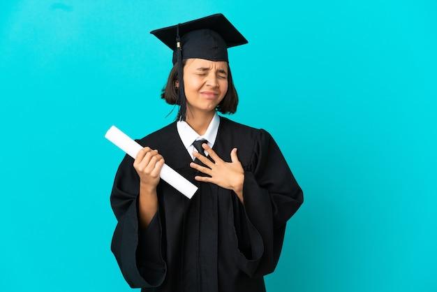 Giovane ragazza laureata su sfondo blu isolato che ha un dolore nel cuore