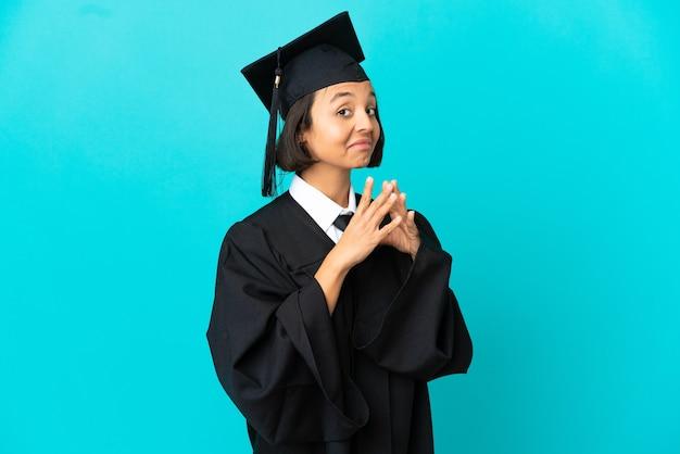 Giovane ragazza laureata su sfondo blu isolato che trama qualcosa