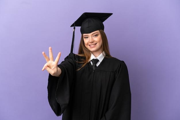 Giovane laureato su sfondo viola isolato felice e contando tre con le dita