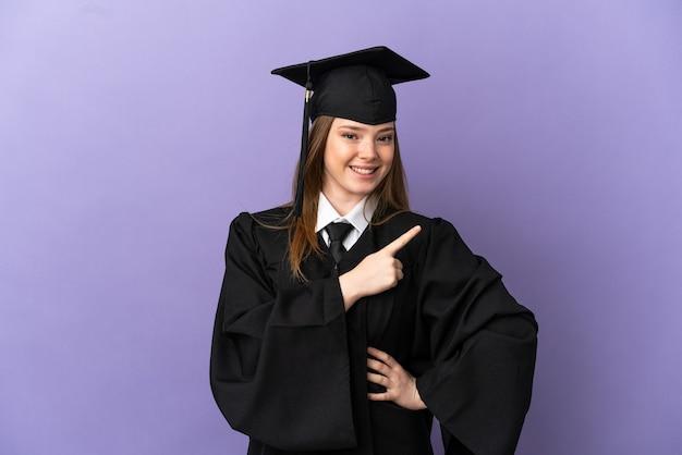 Giovane laureato su sfondo viola isolato che punta al lato per presentare un prodotto