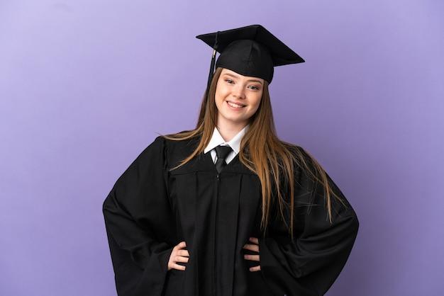 Giovane laureato su sfondo viola isolato in posa con le braccia all'anca e sorridente