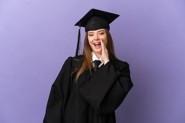 Giovane laureato su sfondo viola isolato che grida con la bocca spalancata