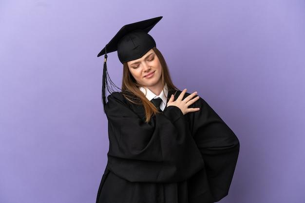 Giovane laureato su sfondo viola isolato che soffre di dolore alla spalla per aver fatto uno sforzo