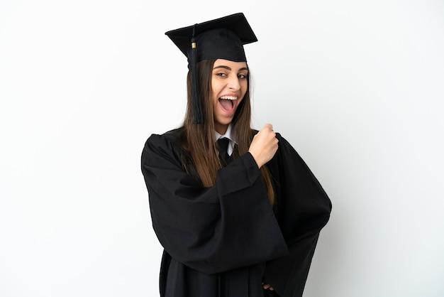 Giovane laureato isolato su sfondo bianco che celebra una vittoria