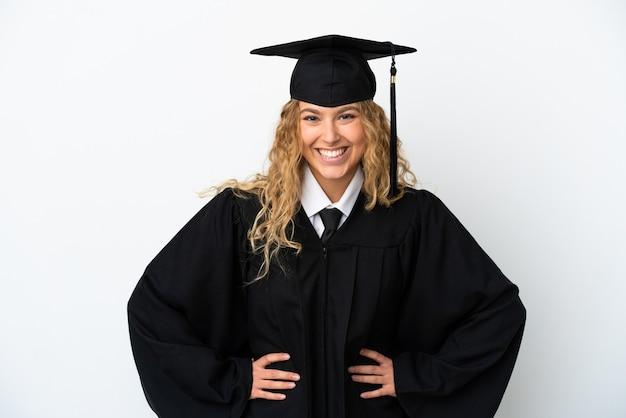 Giovane laureato isolato su sfondo bianco in posa con le braccia all'anca e sorridente