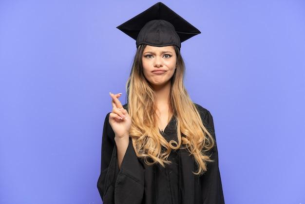 Giovane laureata ragazza russa isolata su sfondo bianco con le dita incrociate e augurando il meglio