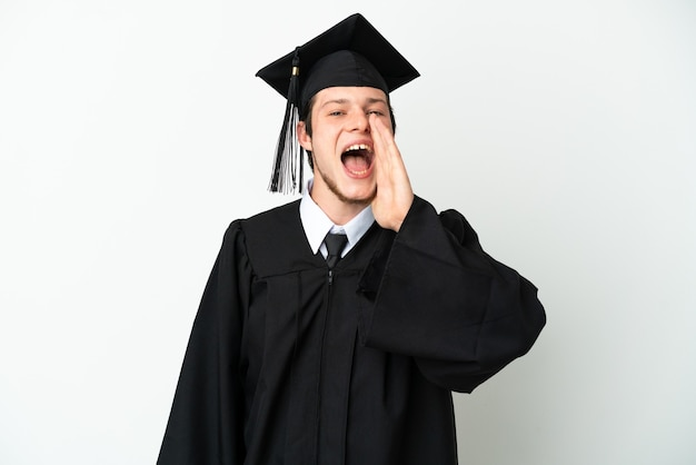 Giovane laureato russo dell'università isolato su fondo bianco che grida con la bocca spalancata
