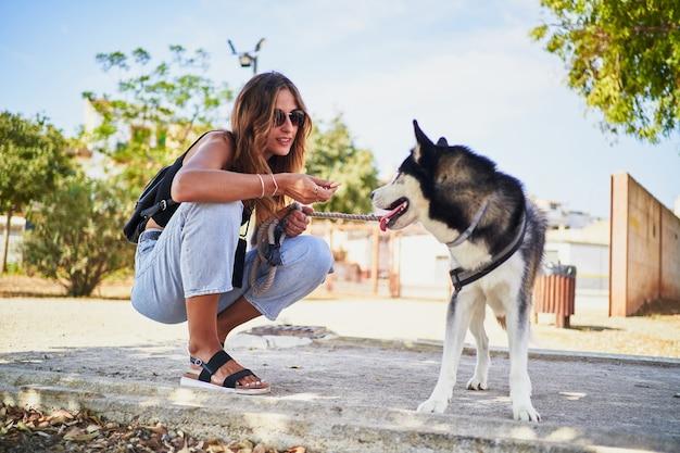 Giovane donna irriconoscibile che offre un biscotto al suo husky siberiano nel parco