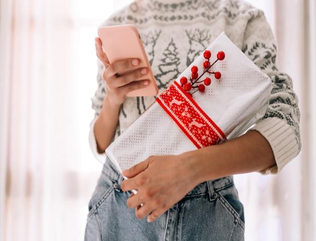 Giovane donna irriconoscibile che guarda il suo cellulare tenuto in una confezione regalo in carta metallizzata