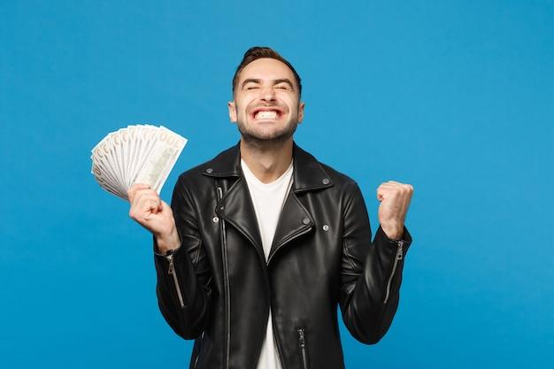 Giovane uomo con la barba lunga in giacca di pelle nera t-shirt bianca che tiene ventaglio di denaro contante in banconote in dollari isolate su sfondo blu muro ritratto in studio. concetto di stile di vita della gente. mock up copia spazio.