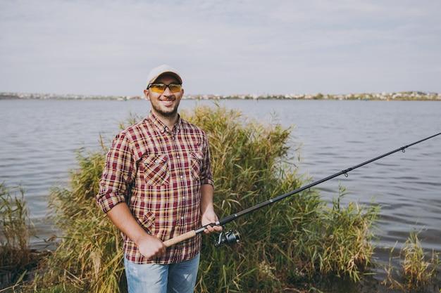 Il giovane uomo sorridente con la barba lunga in camicia a scacchi, berretto e occhiali da sole tiene la canna da pesca sulla riva del lago sullo sfondo di acqua, arbusti e canne. stile di vita, ricreazione, concetto di svago del pescatore.