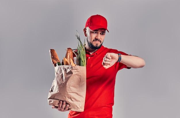 Il giovane uomo di consegna barbuto sconvolto in uniforme rossa tiene un pacchetto con pane e verdure e guarda lo smartwatch sulla sua mano che è in ritardo isolato su sfondo grigio.