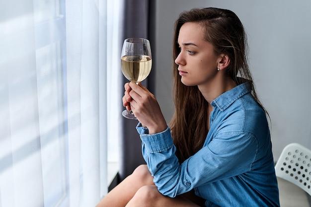 La giovane donna disperata malinconica depressa sola turbata con gli occhi tristi in una camicia tiene il bicchiere di vino e si siede da solo a casa dalla finestra durante la depressione e le preoccupazioni. problemi di vita