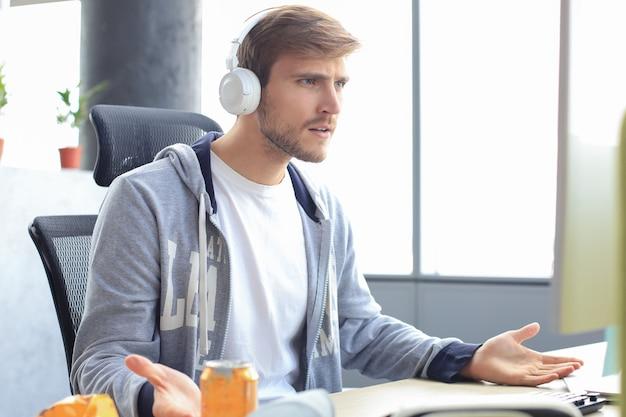 Giovane giocatore sconvolto che gioca ai videogiochi online sul computer e si sente depresso.