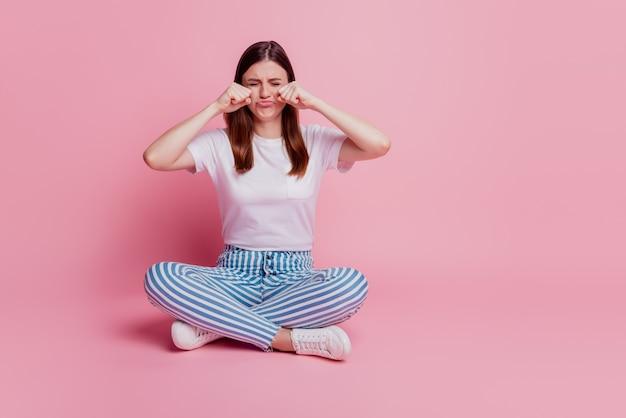 Giovane ragazza sconvolta sedersi sul pavimento gambe incrociate piangere umore frustrato piangendo i pugni faccia