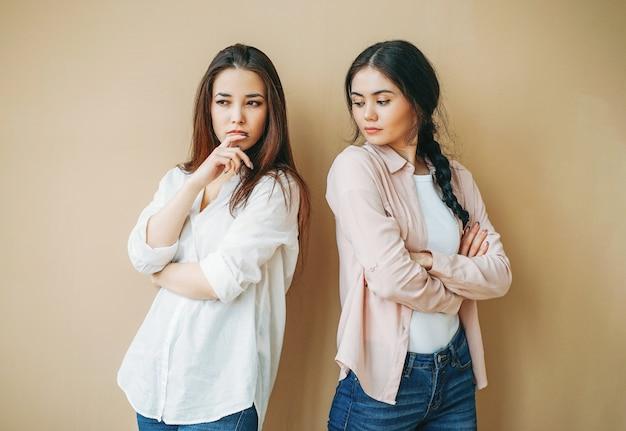 Amici di ragazze turbati dei giovani in offensivo casuale a vicenda isolato su fondo beige, concetto di gelosia