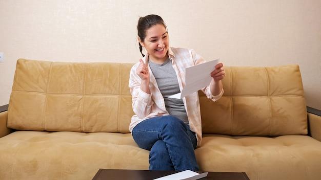 La giovane donna sconvolta prende il documento cartaceo dalla busta e diventa gioiosa con le buone notizie seduta su un comodo divano beige in un soggiorno luminoso