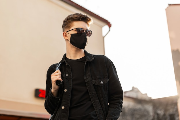 Modello di giovane uomo urbano alla moda in giacca di jeans nera alla moda con zaino in occhiali da sole vintage