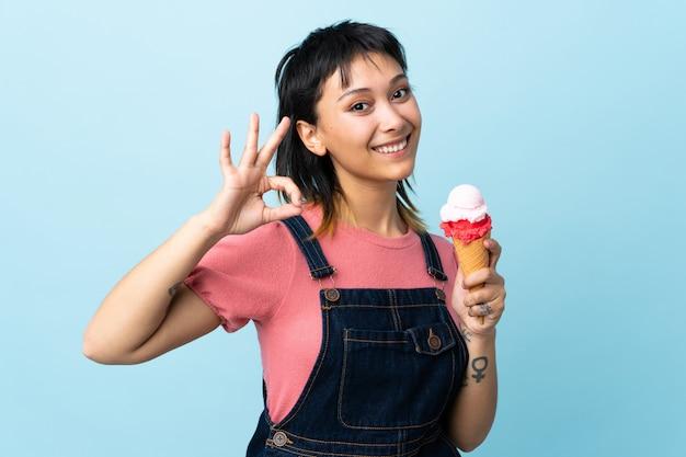 Giovane ragazza uruguaiana che tiene un gelato della cornetta sopra la parete blu isolata che mostra segno giusto con le dita