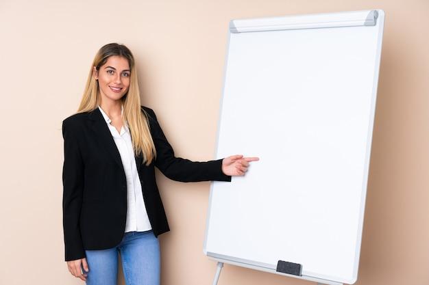 Giovane donna uruguaiana che dà una presentazione sul bordo bianco e che lo indica