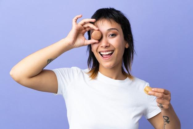 Giovane donna uruguaiana sopra la parete viola isolata che tiene i macarons francesi variopinti
