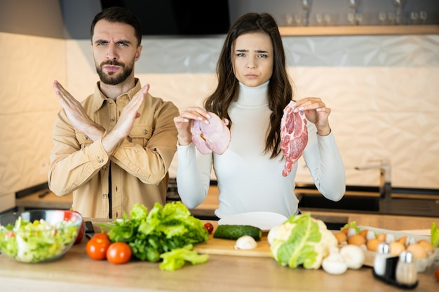 La giovane coppia vegetariana sta dimostrando che non gli piace mangiare carne e preferisce le verdure fresche