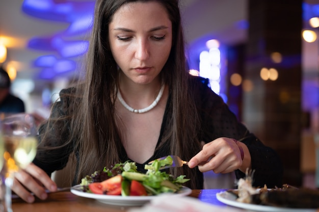 Giovane donna vegetariana che mangia insalata al ristorante.