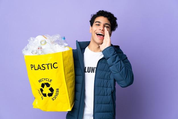 Giovane venezuelano che tiene una borsa piena di bottiglie di plastica che grida con la bocca spalancata