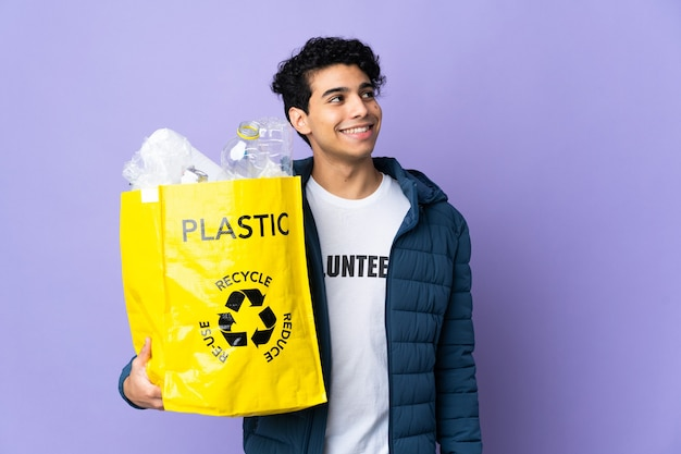 Giovane uomo venezuelano che tiene una borsa piena di bottiglie di plastica pensando un'idea mentre guarda in alto