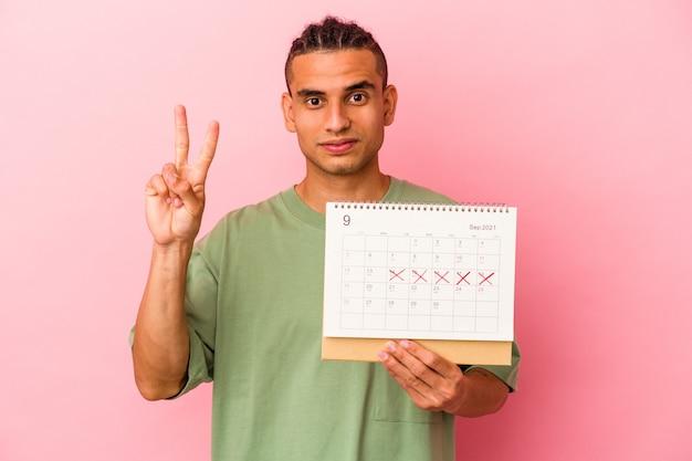 Giovane uomo venezuelano che tiene un calendario isolato su sfondo rosa che mostra il numero due con le dita.