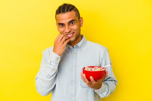 Giovane uomo venezuelano che tiene una ciotola di cereali isolata su sfondo giallo che si morde le unghie