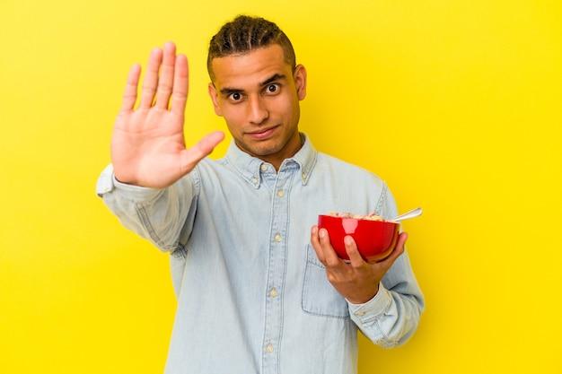 Giovane uomo venezuelano che tiene una ciotola di cereali isolata su sfondo giallo