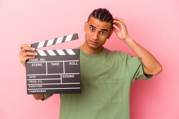 Giovane uomo venezuelano con in mano un ciak isolato su sfondo rosa scioccato, ha ricordato un incontro importante.