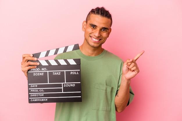 Giovane uomo venezuelano che tiene un ciak isolato su sfondo rosa sorridente e rivolto da parte, mostrando qualcosa in uno spazio vuoto.