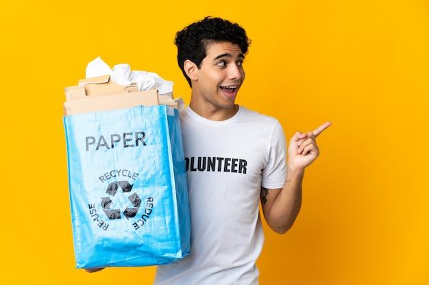 Giovane venezuelano che tiene un sacchetto per il riciclaggio pieno di carta da riciclare con l'intenzione di realizzare la soluzione sollevando un dito