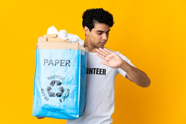 Giovane venezuelano che tiene un sacchetto di riciclaggio pieno di carta per riciclare facendo gesto di arresto e deluso