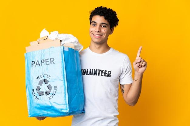 Giovane venezuelano che tiene un sacchetto di riciclaggio pieno di carta da riciclare mostrando e alzando un dito in segno del meglio