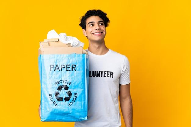 Giovane uomo venezuelano che tiene un sacchetto di riciclaggio pieno di carta per riciclare pensando un'idea mentre guarda in alto